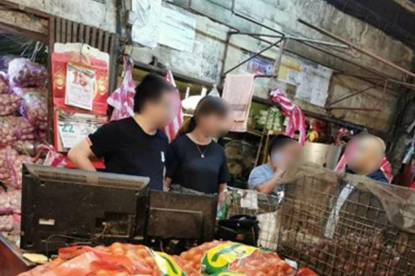 Immigration agents apprehend two Chinese nationals illegally working as vendors in Divisoria in Manila on Monday