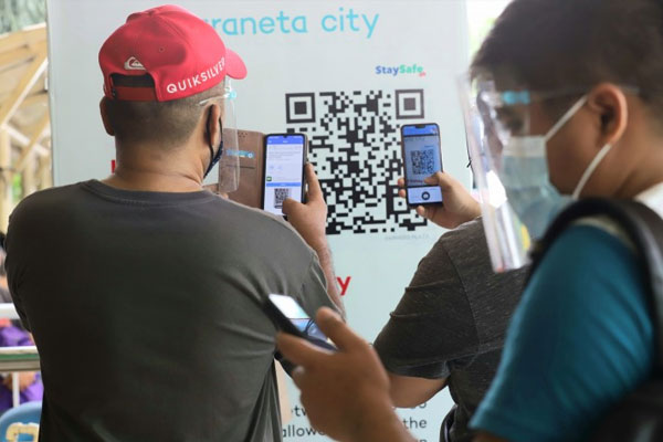 Visitors stand at the mall's entrance as they scan the QR code and fill-up the registration using their smartphones for the digital contact tracing platform application being implemented in some establishments at the Araneta Center in Cubao, Quezon City on Tuesday (Feb. 23, 2021) / PNA