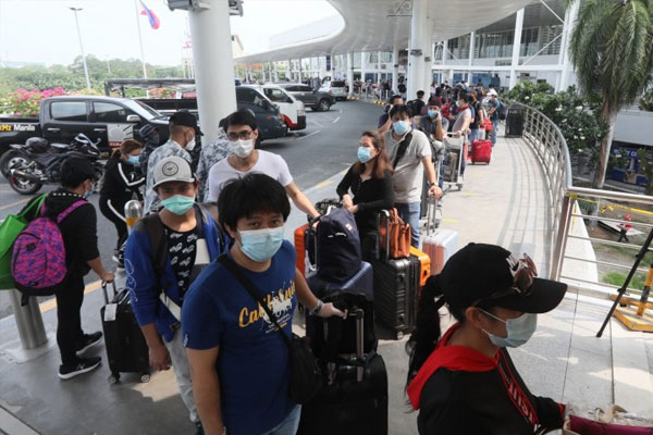 Overseas Filipino workers (OFWs) heading to their hometowns after completing mandatory quarantine queue at the departure area of Ninoy Aquino International Airport Terminal 2 during a send-off on Tuesday (May 26, 2020) / PNA