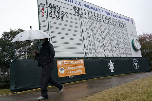 A person carries an umbrella while walking next to a sign advising that play is temporarily suspended during a weather delay in the final round of the US Womens Open golf tournament.DAVID J. PHILLIP/ASSOCIATED PRESS