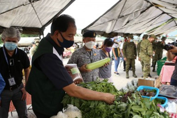 Agriculture Secretary William Dar (2nd from left) and AFP deputy chief-of-staff Lt. Gen. Antonio Ramon Lim (with black beret) look at vegetables and other agricultural products sold at the Kadiwa retail store in Camp Aguinaldo, Quezon City on Saturday (July 11, 2020) / PNA / AFP