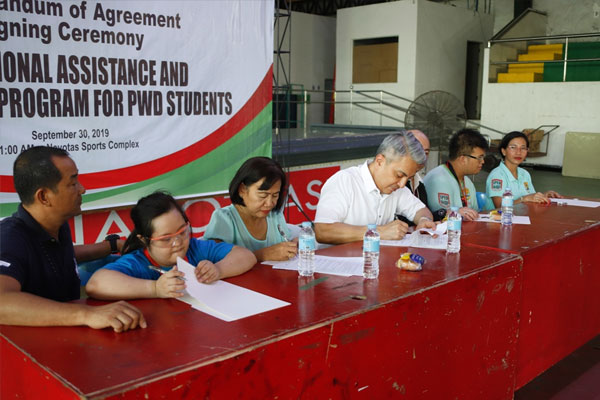 Navotas City Mayor Toby Tinagco signs MOA with the beneficiaries of the scholarship program. / Navotas PIO