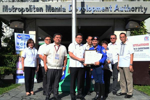 MMDA Chair Danilo Lim congratulates lady traffic enforcer Rowena Capistrano for bagging the Dangal ng Bayan Award-Regional Winner / PIA