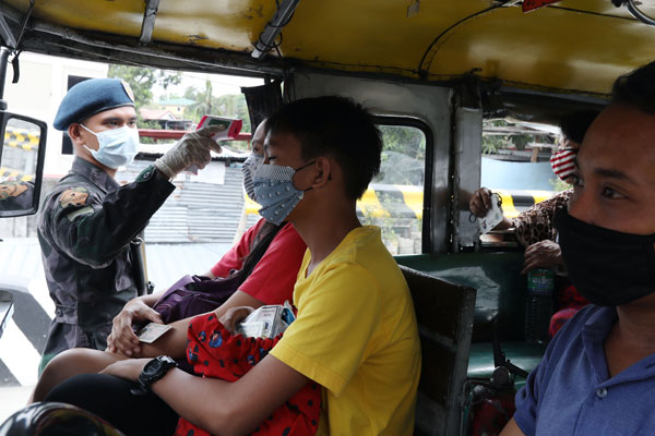 A police personnel checks the temperature of passengers of a jeepney from Caloocan to Bulacan on Sunday (March 15, 2020). The measure is part of the one-month community quarantine implemented in Metro Manila starting Sunday to prevent the spread of the deadly coronavirus. / PNA / Oliver Marquez