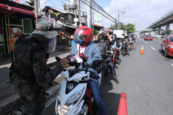 A police officer inspects IDs and other documents presented by motorcycle riders entering Antipolo City, Rizal on Tuesday (May 19, 2020) / PNA