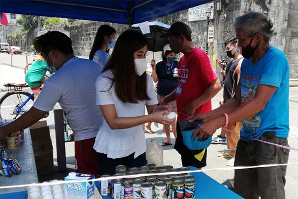 Intramuros, Manila residents distribute food items like eggs, noodles, sardines, rice, and vegetables near the San Agustin Church on Sunday (April 25, 2021) / PNA