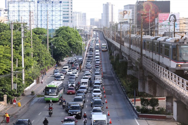 A Metro Rail Transit (MRT)-3 train (right) passes by as vehicles are stuck in traffic congestion along the Edsa southbound lane near the Kamuning Flyover in Quezon City on Monday (June 1, 2020) / PNA