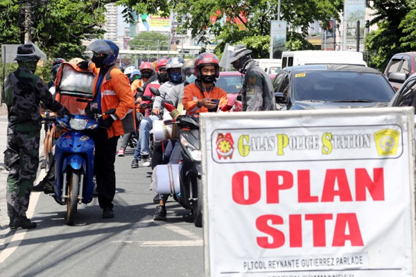 Quezon City Police District (QCPD) personnel inspect IDs of motorcycle riders / PNA