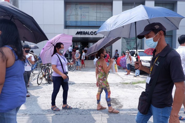 Customers observe physical distancing while queuing to pay their electricity bills at a branch of Meralco along Commonwealth Avenue, Quezon City on Monday (May 18, 2020) / PNA