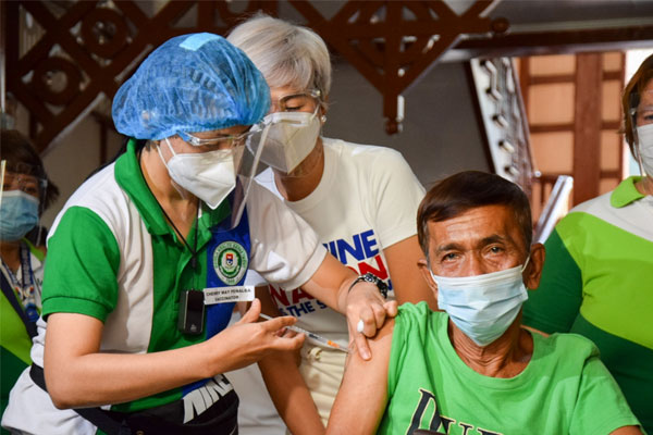 A health worker administers a %u2018Covid-19 vaccine%u2019 to a senior citizen during a simulation at the Legarda Elementary School in Manila on Thursday (Feb. 18, 2021) / Manila PIO