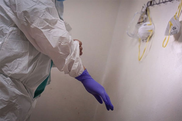 A health worker puts on a double layer of gloves for added protection before handling patients infected by COVID-19 / Photo Courtesy of ABS-CBN
