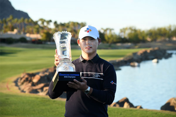 Si Woo Kim of South Korea poses with the trophy after putting in to win on the 18th green during the final round of The American Express tournament on the Stadium course at PGA West on January 24, 2021 in La Quinta, California. Harry How/Getty Images/AFP