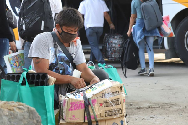 A man who availed of the government's Balik Probinsya, Bagong Pag-asa Program arranges his boxed pieces of luggage for loading into a bus en route to Leyte on Wednesday (May 20, 2020) / PNA
