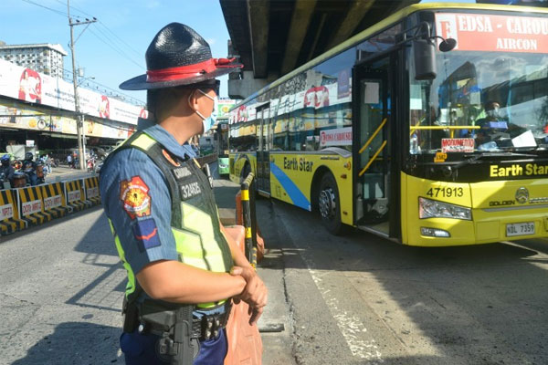A Philippine National Police-Highway Patrol Group (PNP-HPG) officer mans the center island at the Nepa Q-mart carousel bus station along Edsa in Quezon City on Tuesday (March 30, 2021) / PNA