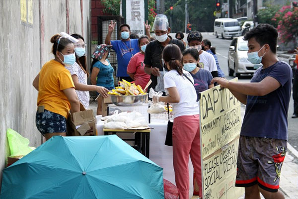 Several Quezon City residents line up to get free food items like rice, noodles, and canned goods at a community pantry put up along Dapitan Street in Quezon City on Saturday (April 24, 2021) / PNA