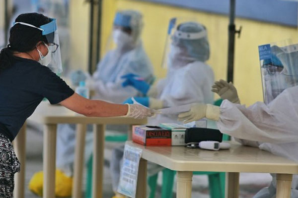 A Manila resident hands over a paper to a health worker after submitting to COVID-19 mass swab testing at a quarantine center / Photo Courtesy of Mike Alquinto/BenarNews
