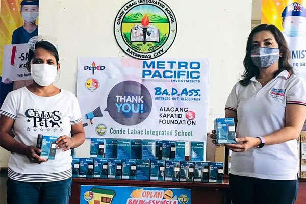 Empowering Education through Connecting Communities. Metro Pacific Investments Foundation President Melody del Rosario (right) turns over of fifty Smart Pocket Wi-Fis to the student scouts of  Conde Labac Integrated School / MPIC