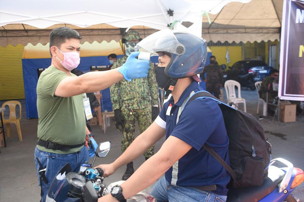 A school nurse deployed in San Pedro %u2013 Muntinlupa boundary conducting a temperature check. The local government of Muntinlupa has drafted nurses assigned in public schools to serve as additional medical personnel in local quarantine control points.