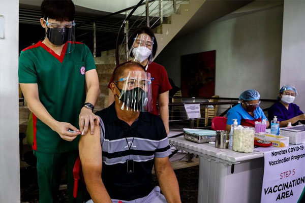 Reygalicano Nepomuceno, 64, receives the first dose of Pfizer-BioNTech vaccine at Navotas City Hospital. Nepomuceno is among the 152 Navote%uFFFDos who signed up at http://covax.navotas.gov.ph,  and chose the said vaccine and set his vaccination schedule.