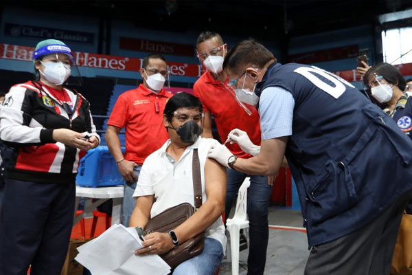 Health Secretary Francisco Duque III administers a Covid-19 vaccine to an adult with comorbidities as San Juan City rolls out the vaccination for senior citizens and adults with comorbidities on Tuesday (March 30, 2021) / PNA