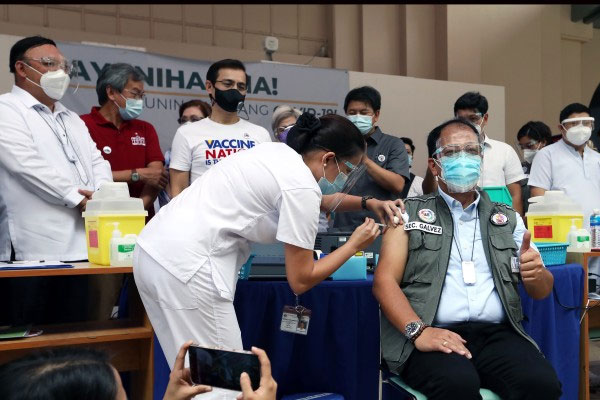 Secretary Carlito Galvez Jr., National Policy Against Covid-19 chief implementer and vaccine czar, shows the thumbs-up sign as Nurse Maan Villanueva administers the CoronaVac vaccine at the University of the Philippines-Philippine General Hospital (UP-PGH) in Manila City on Monday (March 1, 2021) / PNA