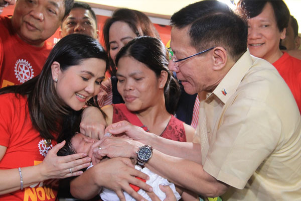 Health Secretary Francisco III administers polio vaccine to a child after the ceremonial signing of Agreement with the Rotary International to strengthen drive against polio. / DOH