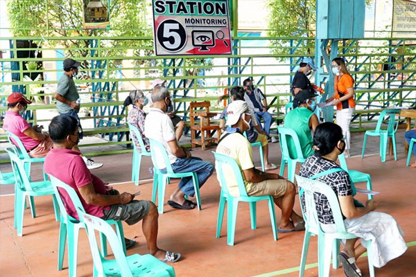 Senior citizens who received the Covid-19 vaccine remain at the monitoring station of Bagong Silang Elementary School, Caloocan City to be observed for 15to 30 minutes if the vaccine had an adverse effect on them. / PNA