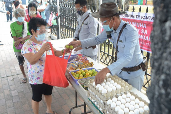 Intramuros, Manila joins the community pantry fray on Monday (April 19, 2021). Tables are set up outside the Manila Cathedral with assorted food items being distributed with the help of two security personnel. (PNA photo by Avito C. Dalan)
