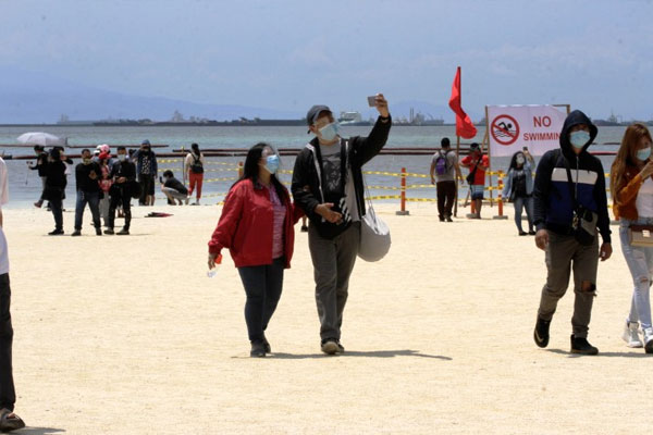 People take selfies at Manila Bays white sand beach on Roxas Boulevard on Sunday (Sept. 20, 2020) / PNA