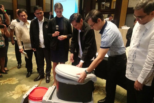Secretary Roy A. Cimatu and Manila Mayor Isko Moreno demonstrate how to use the portable toilet that will be distributed to the residents of Parola, Tondo for the Project: Kubeta Ko. / Photo Courtesy of DENR