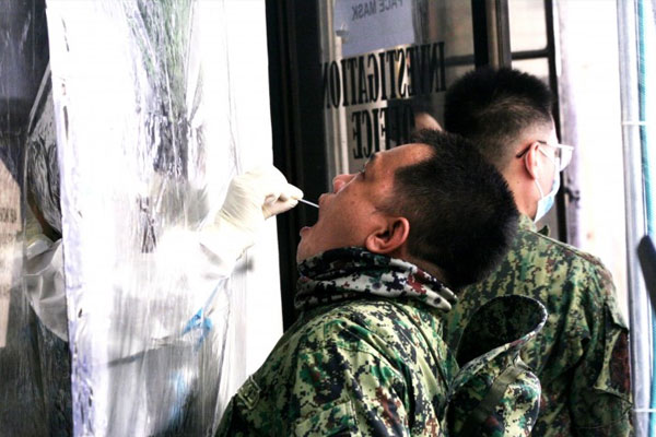 A member of the Station Investigation and Detection Management Unit of the Southern Police District (SPD) undergoes swab testing at the SPD headquarters in Pasay City on Monday (June 22, 2020) / PNA