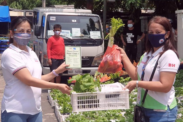 Metro Pacific Investments Foundation President Melody del Rosario (L), turns over 100 Bayan Tanim! planting crates to Brgy. 128 Smokey Mountain in Tondo. / MNC Photo File