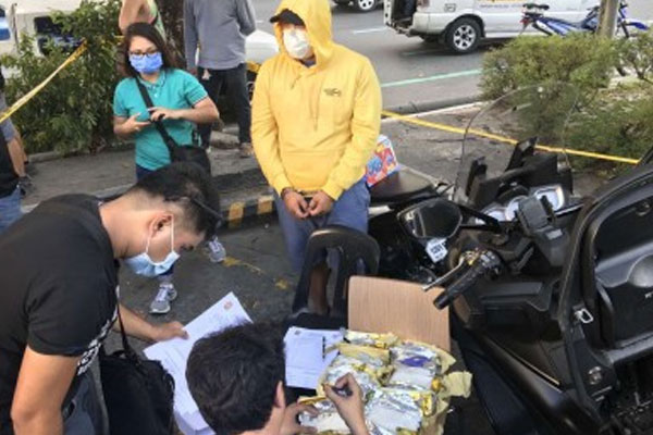 A police officer inspects the shabu seized from drug suspect Mark Anthony Gregorio Carlos (in yellow hoodie) during a buy-bust operation in Quezon City on Wednesday (March 11, 2020) / NCRPO / PNA