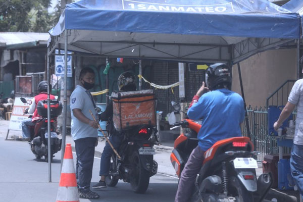A man inspects motorcycle riders entering San Mateo town at a checkpoint along Batasan-San Mateo Road in Rizal on Wednesday (May 27, 2020) as part of protocols and health measures to prevent the further spread of the coronavirus disease 2019 / PNA