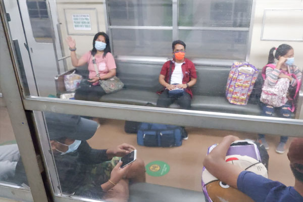 A locally stranded individual (left) waves goodbye aboard the Philippine National Railways (PNR) train that would take her home to Bicol, at the Tutuban Station in Manila early Saturday (June 20, 2020) / PNA